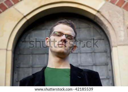 Serious young man`s face. In background big door.