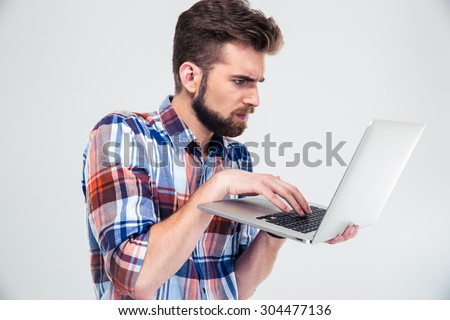 Serious young man standing and using laptop isolated on a white background - stock photo