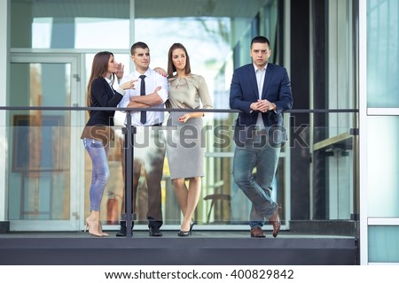 Serious young man standing in front of his business team, while other employees talking behind his back