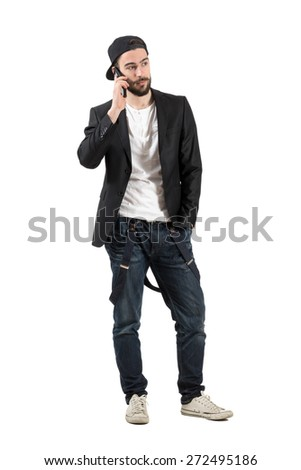 Serious young man talking on the cellphone wearing hat backwards. Full body length portrait isolated over white background.  - stock photo