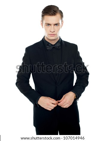 Serious young man tucking coat button isolated over white background