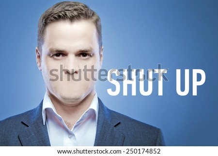 Serious young man without a mouth on a blue background with the words: Shut Up - stock photo