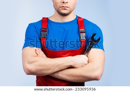 Serious young mechanic in red overall on blue background. closeup of man holding wrench and holding hands crossed - stock photo