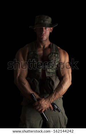 Serious young muscular soldier with gun and flashlight in green uniform standing proud isolated on black background. Army, security and protection. - stock photo