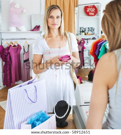 Serious young woman buying clothes looking at the camera in a shop
