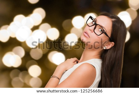 Serious Young Woman Posing against an abstract light background