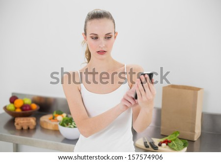Serious young woman sending a text in the kitchen at home - stock photo