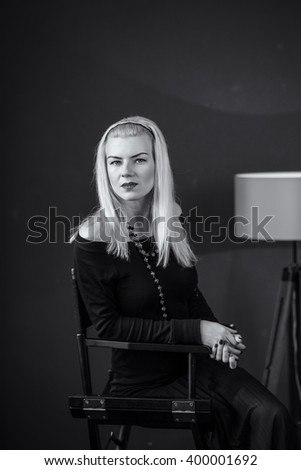 Serious young woman sitting on a chair in the studio floor lamp red lips lipstick look a serious sadness black and white. a psychological portrait, looking right