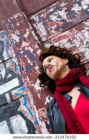 Serious young woman standing at graffiti wall on the street.  - stock photo