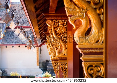 Serpent King statue in buddhist temple. Naga Statue in a Temple, Chiang Mai, Thailand. Golden Naga statue on pillar at Thai Buddhist temple - stock photo