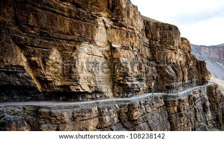 serpentine road in a rock - stock photo
