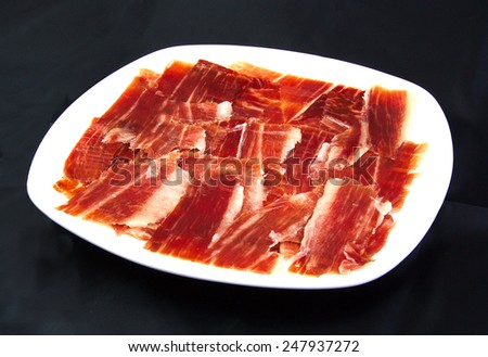 Serrano ham slices on a white dish over black wackground. Jabugo. Spanish tapa - stock photo