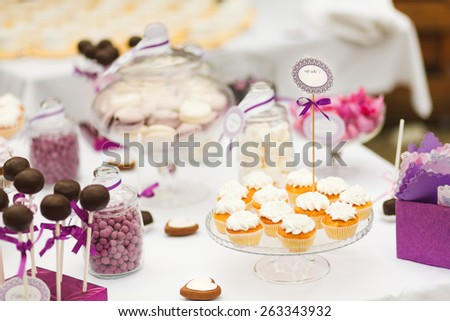 Served festive candy bar table with cupcakes and other desserts - stock photo