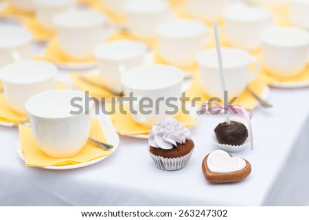 Served festive table with lots of tea cups, cupcake and other desserts - stock photo