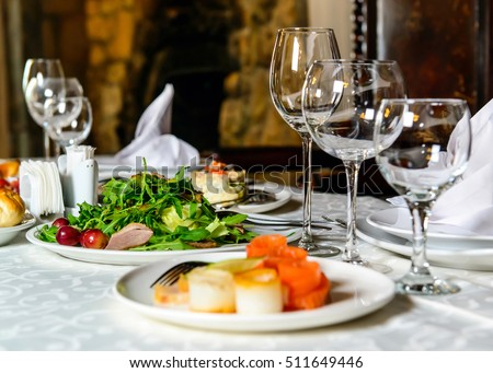 Served for holiday banquet restaurant table with dishes, snack, cutlery, wine and water glasses, european food, selective focus