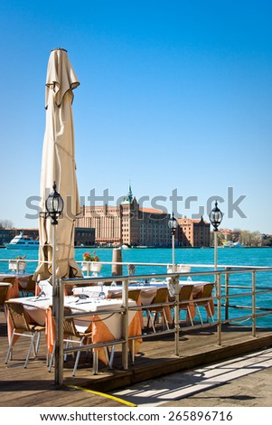 Served glasses of tables in outdoore cafe in Venice, Italy - stock photo