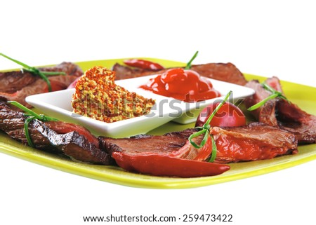 served meat slices on green dish with spices - stock photo
