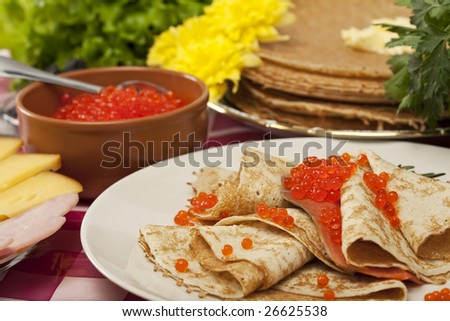 served place setting: pancake with red caviar and greens