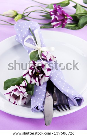 Served plate with napkin and flowers close-up - stock photo