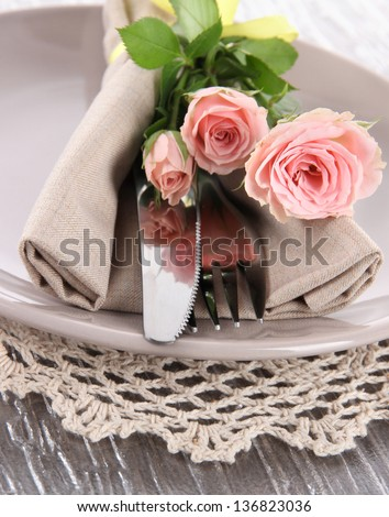 Served plate with napkin and rose close-up - stock photo