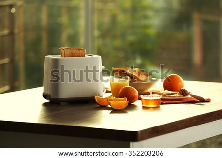 Served table for breakfast with toast and orange juice, on blurred background - stock photo