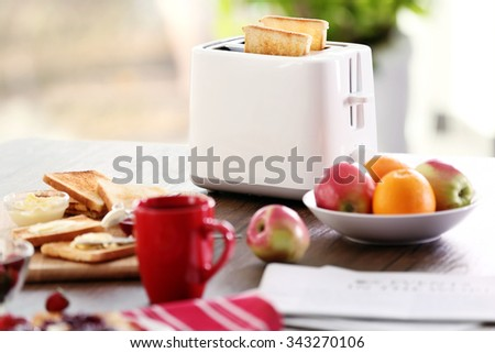 Served table for breakfast with toast, coffee and fruit, on blurred background - stock photo