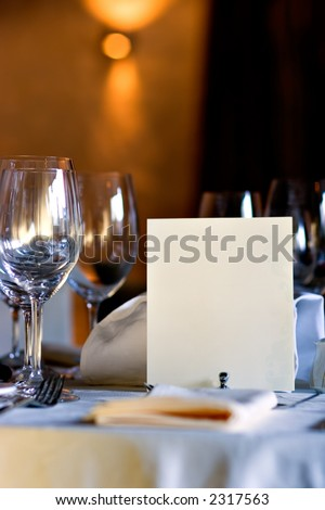 Served table in restaurant interior, with blank menu, with copy space