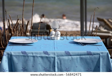 served tables in beach restaurant, sea background - stock photo