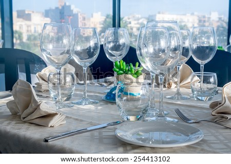 Served tables with empty plates and glasses in luxury restaurant. - stock photo