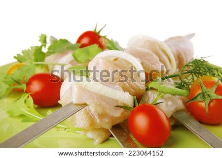 served uncooked chicken kebabs with raw vegetables - stock photo