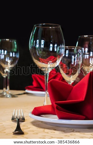 Served white plate with fork and wine glasses. red napkin. black background, soft focus - stock photo