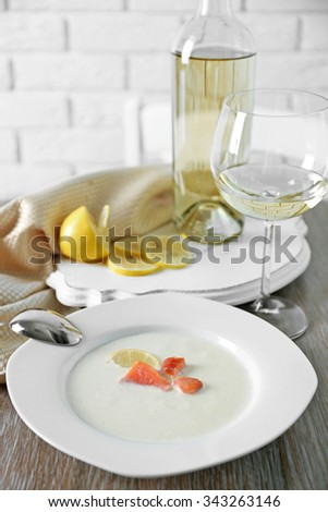 Served wooden table with tasty salmon cream soup, wine and lemon on it, close up