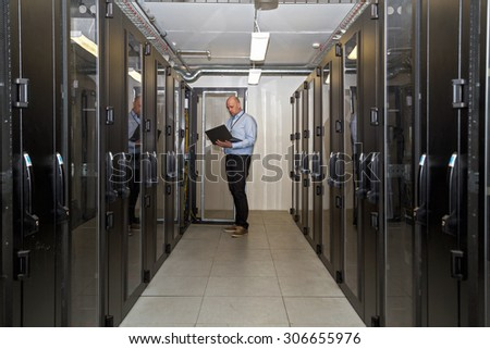 Server administrator working late on updating servers in a server room outside office hours, holding a laptop to check on progress - stock photo