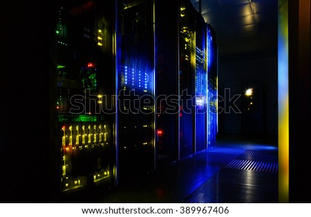 server room in dark, with bright colored lights - stock photo