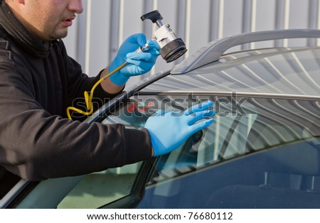 service agent  repairs dangerous crack in windhield on location without replacement glass for free, Smart repair - stock photo