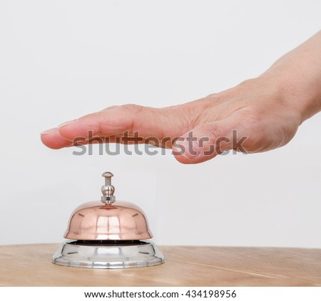 Service Bell. Person using their palm to ring a counter bell.