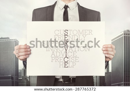 Service crossword concept on paper what businessman is holding on cityscape background