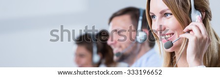Service desk consultant talking on hands-free phone - stock photo