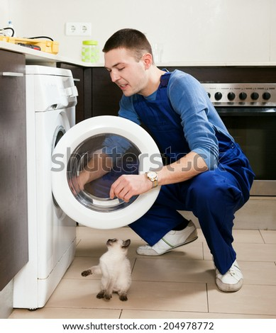 Service worker repairing washing machine at kitchen - stock photo