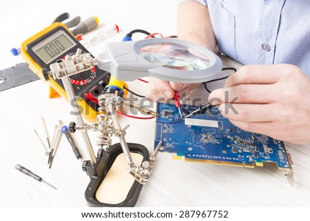 Serviceman checks PCB with a digital multimeter in the service workshop - stock photo