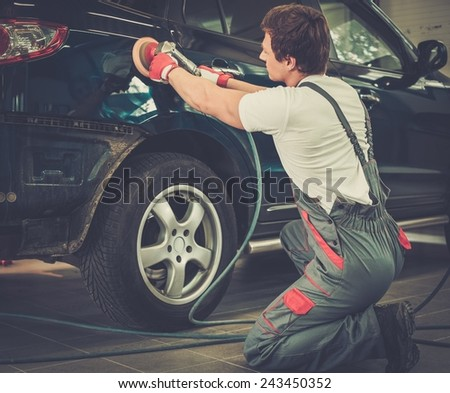 Serviceman polishing car body with machine  in a workshop - stock photo