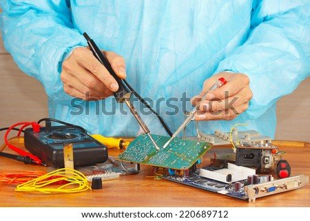 Serviceman solder electronic board of device in the service workshop - stock photo