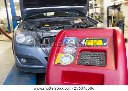 Servicing car air conditioner in auto repair shop - stock photo