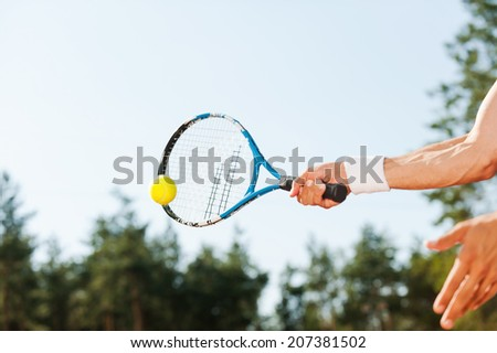 Serving ball. Close-up of male tennis player serving ball  - stock photo