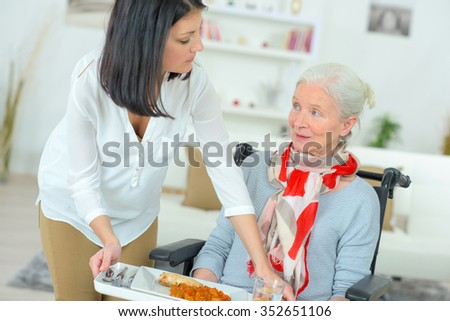 Serving disabled woman her meal - stock photo