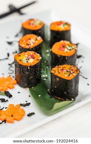 serving fresh raw vegetarian rolls with carrot - stock photo