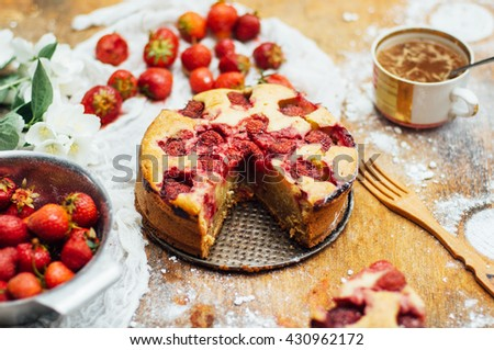 Serving homemade strawberry cake or pie on wooden rustic table. Tart with fresh strawberry on wooden background. Strawberry tart  with icing sugar and whole fruits onwith cooking utensils. Rustic styl - stock photo