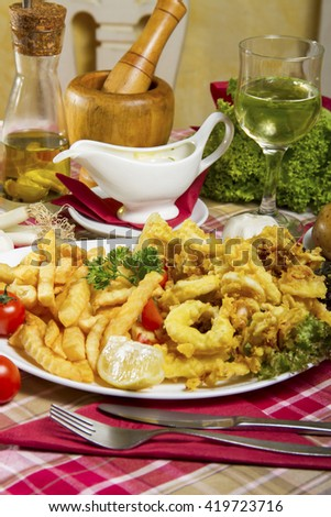 Serving of breaded and deep-fried calamari and fries on a white plate served on a table with dressing sauce, edible oil, lemon and a glass of white wine. - stock photo