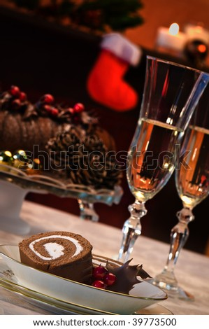 Serving of chocolate swiss roll with champagne in artistic Christmas setting - stock photo