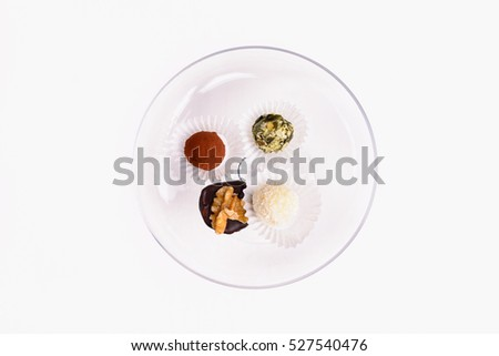 Serving of decorative petit fours and fondant bonbons on a white plate viewed from above for a tasty Christmas or festive dessert isolated on white